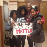 A group of holds a Black Lives Matter Sign